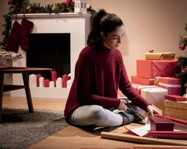 Mujer de ángulo bajo en casa envolviendo regalos