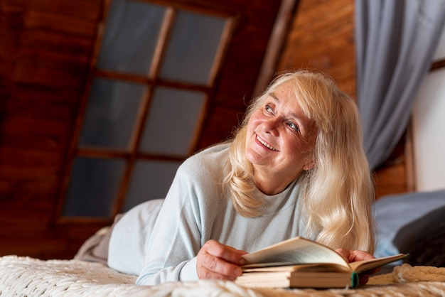 Mujer de ángulo bajo en casa leyendo