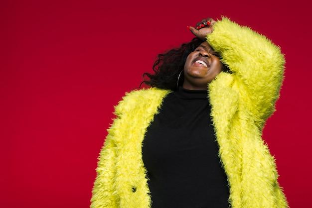 Mujer de ángulo bajo con chaqueta amarilla
