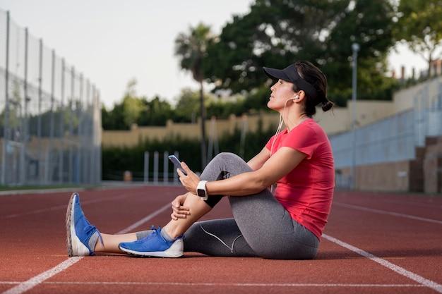 Mujer de ángulo bajo descansando después de correr