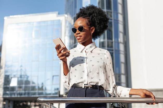 Mujer de ángulo bajo con gafas de sol y teléfono