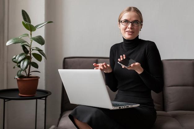 Mujer de ángulo bajo con laptop y móvil