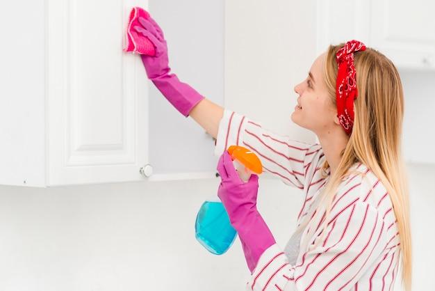 Mujer de ángulo bajo, limpieza de paredes en casa