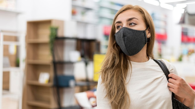 Mujer de ángulo bajo con máscara en compras