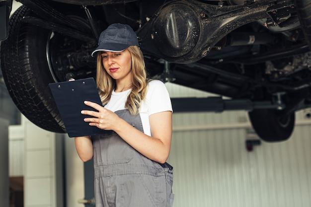 Mujer de ángulo bajo mecánico inspeccionando coche
