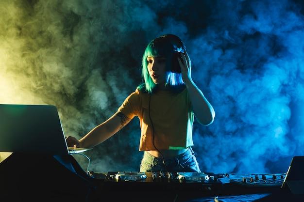 Mujer de ángulo bajo mezcla en maqueta de club