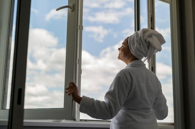 Mujer de ángulo bajo mirando por la ventana