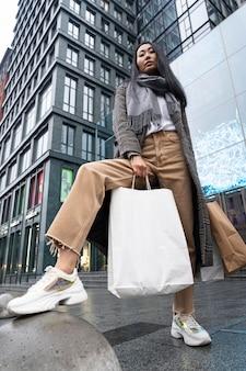 Mujer de ángulo bajo posando con bolsas de la compra.