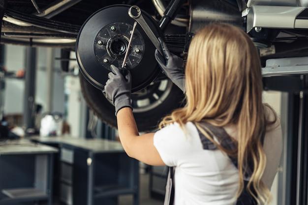 Mujer de ángulo bajo reemplazando las ruedas del automóvil