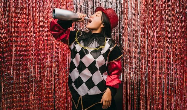 Mujer de ángulo bajo en traje con botella de champagne