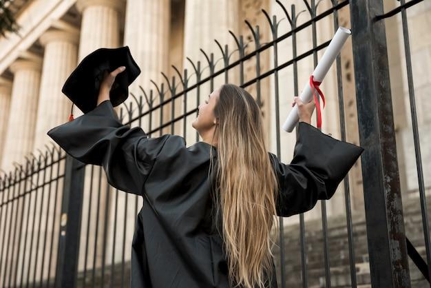 Mujer de ángulo bajo con vestido académico.