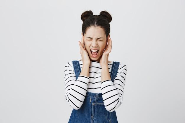 Mujer angustiada cierra los oídos y grita