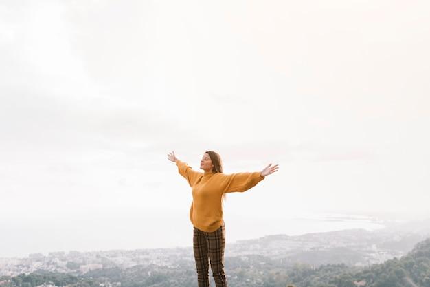 Mujer animada disfruta la hermosa vista en el pico de la montaña contra el cielo