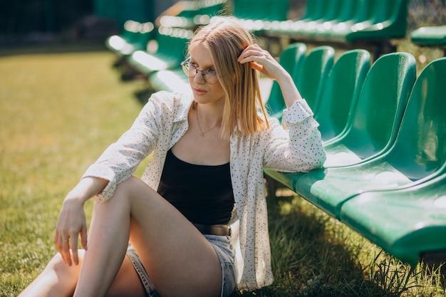 Mujer animadora sentada en el campo de fútbol