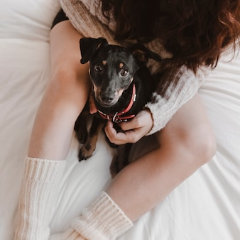 Mujer anónima con perro en la cama