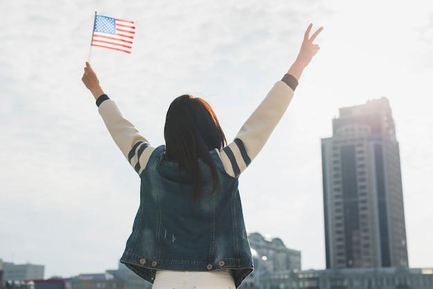 Mujer anónima levantando manos y bandera estadounidense en honor al día de la independencia