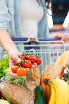 Mujer anónima que sostiene los tomates que se colocan con el carro de la compra en el supermercado