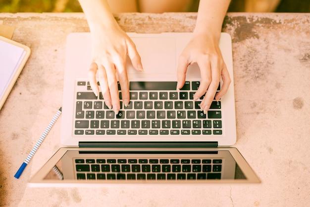 Mujer anónima sentada en el escritorio y escribiendo en la computadora portátil