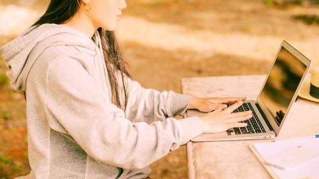Mujer anónima en sudadera con capucha acogedora sentada y escribiendo en una computadora portátil