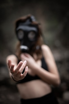 Mujer anónima vestida de negro y máscara de gas en el increíble bosque espeluznante