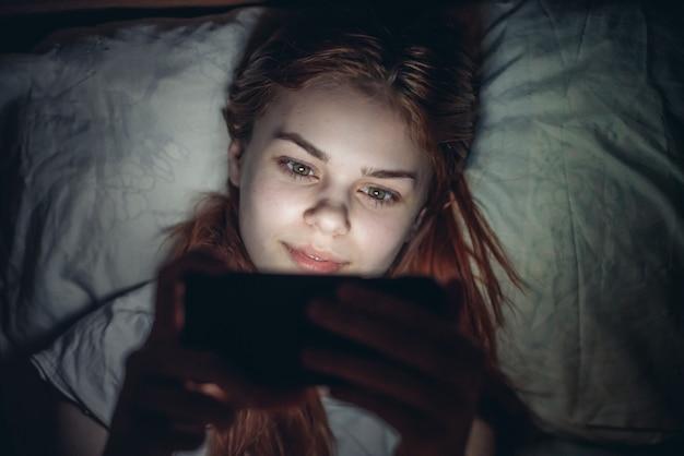 Mujer antes de acostarse con un teléfono en sus manos adicción leyendo noticias