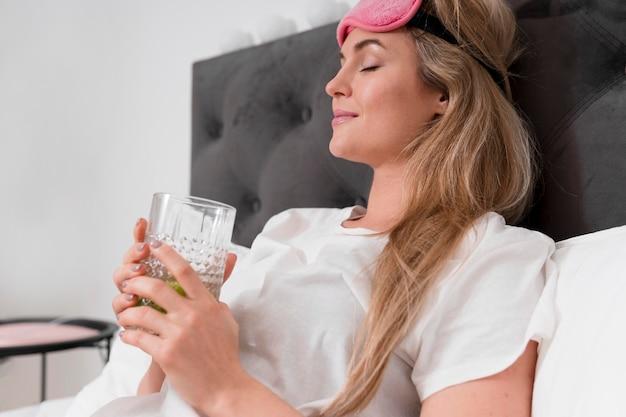 Mujer con antifaz para dormir sosteniendo un vaso de agua