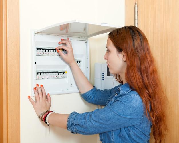 Mujer apagando el interruptor de la luz