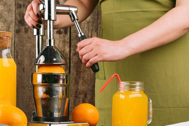 Mujer con aparato exprimidor de naranja en casa