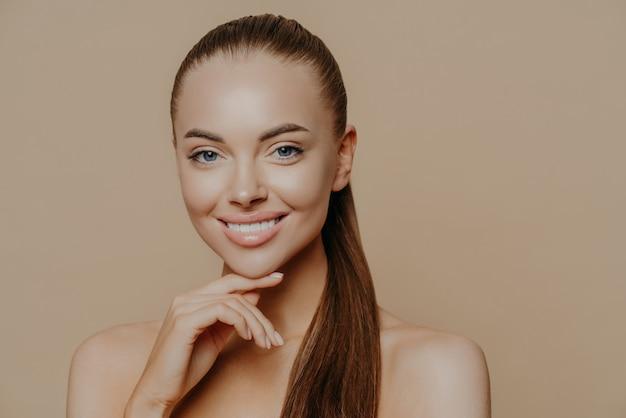 La mujer con apariencia europea tiene una piel pura y sana después de realizar los procedimientos de limpieza diaria.