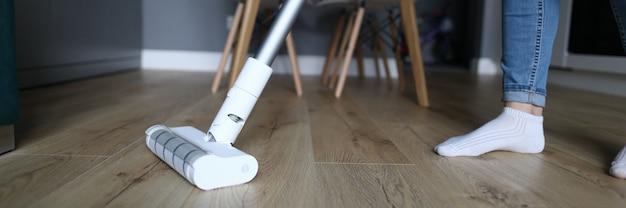 La mujer en el apartamento lava el piso con un trapeador.