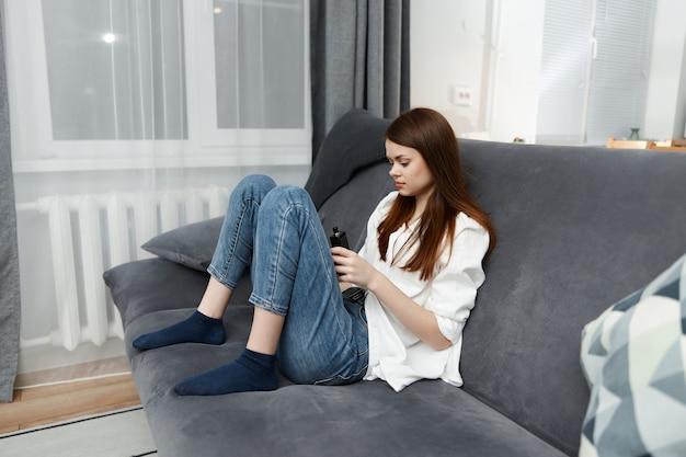 Mujer en un apartamento sentado en un sofá descanso piernas dobladas