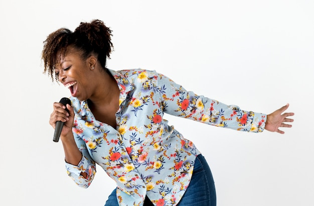 Mujer apasionada negra vocalista cantando karaoke.