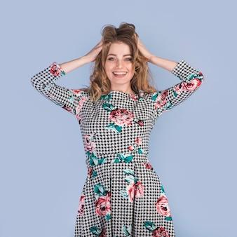 Mujer apasionada positiva en vestido con las manos en el pelo