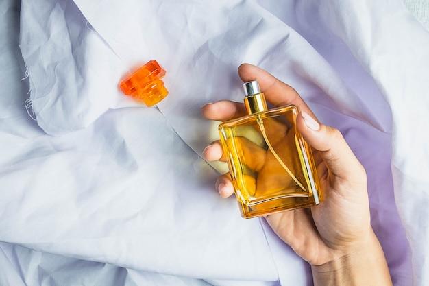 Mujer aplica perfume en su muñeca.