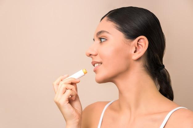 Mujer aplicando bálsamo en los labios