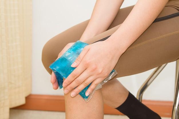 Mujer aplicando compresas frías en la rodilla lastimada hinchada después de una lesión deportiva