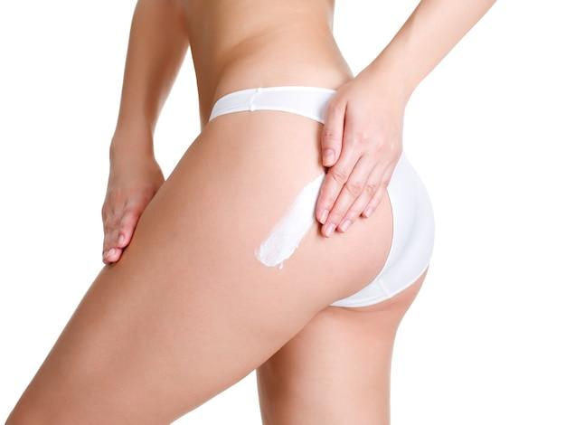 Mujer aplicando crema cosmética de celulitis en la pierna - aislada onwhite