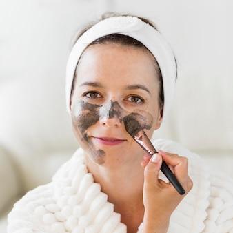 Mujer aplicando crema facial orgánica con pincel de maquillaje