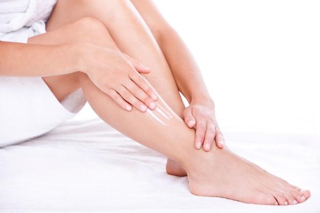 Mujer aplicando crema hidratante en las piernas