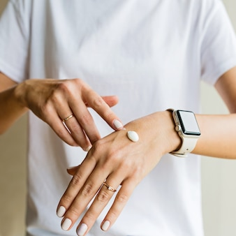 Mujer aplicando crema en mano