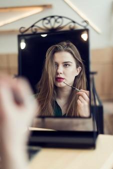Mujer aplicando maquillaje y mirando el espejo