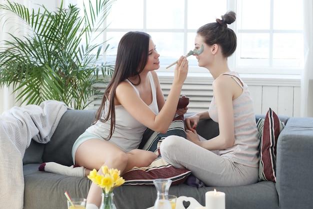 Mujer aplicando una máscara facial a su amiga