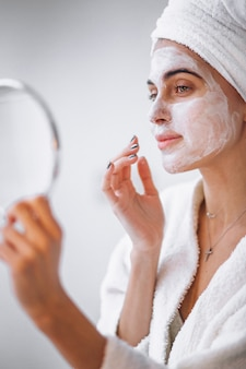 Mujer aplicando mascarilla de belleza
