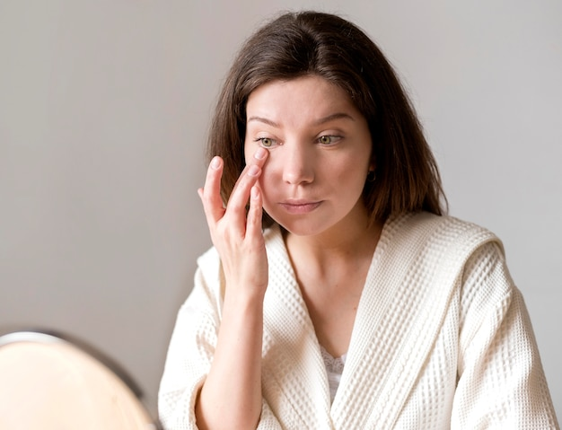 Mujer aplicando ojo concelear con la mano