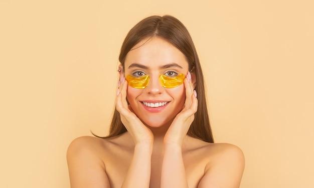 Mujer aplicando parches de ojos dorados. chica de retrato de cerca.