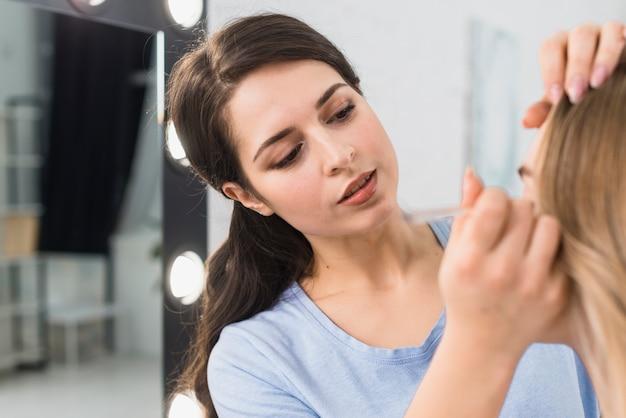 Mujer aplicando pincel delineador de ojos haciendo maquillaje de ojos