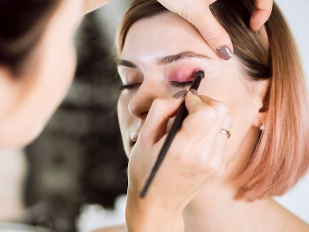 Mujer aplicando sombra de ojos al cliente