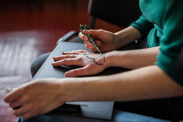 Una mujer aplicando tatuaje mehndi sobre la mano de la mujer.