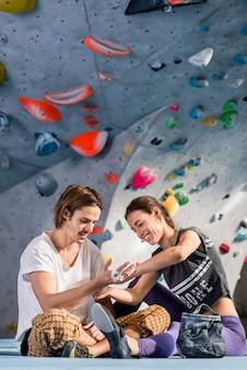 Mujer aplicando vendaje al escalador masculino