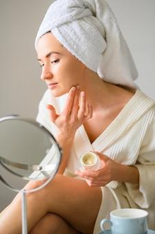 Mujer aplicar crema facial en casa mientras se mira en el espejo